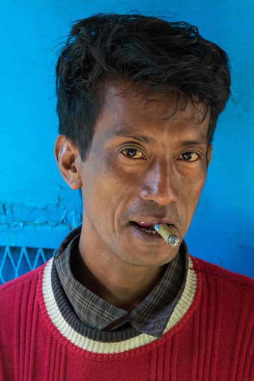 Myanmar/Burma. Portrait of man smoking a cigar at  the Kalaw Train Station.