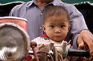 "This young boy is riding in the official ""child seat"" of Asia... in front of his parent on the motorcycle.  Amazing feats of piling 5-7 people on a single scooter have been reported all over Southeast Asia."