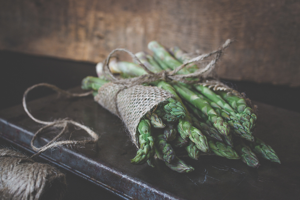 A rustic still life image of asparagus on an old worn baking sheet and a textured backdrop. Subtle green and copper colors draw the eyes to the roll of twine. The highlights from the window on the twine add just the right touch to balance the image and add some interest. Rustic yet simplistic and a lovely addition to any kitchen or dining area. Photographed in my studio.