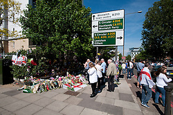 © London News Pictures. 26/05/2013. Woolwich, UK. Members of the public lay flowers, pay tribute and observe the scene where Drummer Lee Rigby was murdered by two men in Woolwich town centre in what is being described as a terrorist attack. Photo credit: Ben Cawthra/LNP
