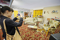 © Licensed to London News Pictures. 15/03/2013 London, UK. A visitor to the Ideal Home Show 2013 photographs a replica of Dell Boy's famous Peckham flat. The Trotters Only Fools and Horses residence has been given a modern makeover by Celebrity designer George Clarke. .Photo credit : Simon Jacobs/LNP