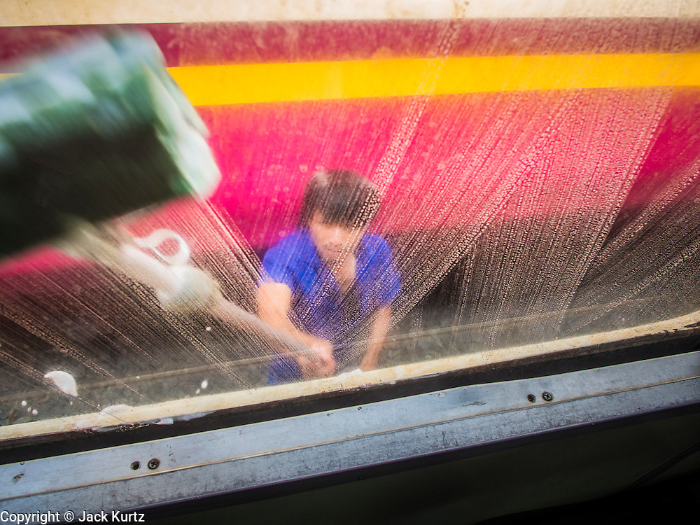 16 APRIL 2014 - BANGKOK, THAILAND: A State Railways of Thailand employee washes the windows on a passenger train in Bangkok. Thai highways, trains and buses were packed Wednesday as Thais started returning home after the long Songkran break. Songkran is normally three days long but this year many Thais had at least an extra day off because the holiday started on Sunday, so many Thais started traveling on Friday of last week.    PHOTO BY JACK KURTZ
