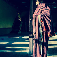 A Buddhist monk in Bhutan in traditional and daily dress.