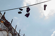 Pairs of shoes hang from wires on a Havana street. Given the relatively low crime rate in Cuba, the symbol probably has a different meaning than in the United States.