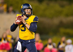 Oct 10, 2015; Morgantown, WV, USA; West Virginia Mountaineers quarterback Skyler Howard rolls out for a pass during the first quarter against the Oklahoma State Cowboys at Milan Puskar Stadium. Mandatory Credit: Ben Queen-USA TODAY Sports