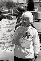 Older woman with poster of the peoples aims for Peoples Park  while National guard take over the town during Student protest & riots in Berkeley California 1969