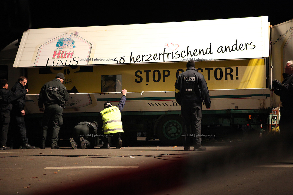 Unrest in Lüchow-Dannenberg. Greenpeace activists blocking an important road by a truck prepared with concrete blocks and chained activists inside. Thousands of people demonstrate against a transport of 11 Castor containers filled with high radioactive waste to Gorleben, Lower Saxony, Germany. The protest takes place shortly after the governments unpopular decision to extend the period of operation for german nuclear power plants for an additional decade.