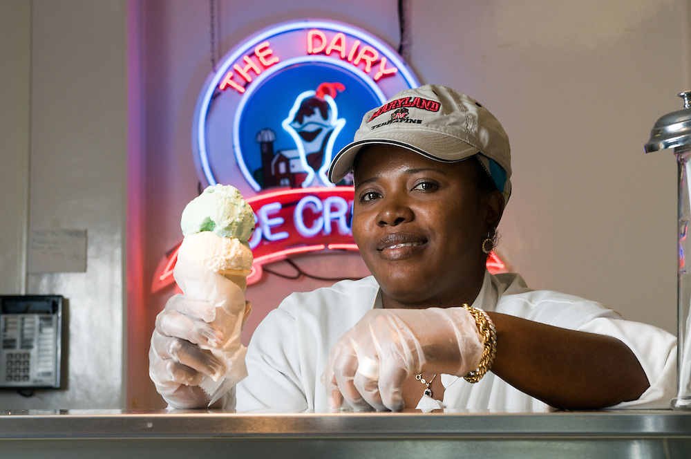 Woman serving ice cream cone behind a dairy counter