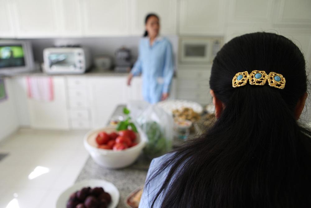 Filipino women dressed in their light blue worker's prepare dinner in their employers' kitchen.