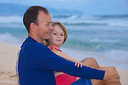 A little girl, safe in her daddy's arms,   on the beach on Oahu's north shore, Hawaii