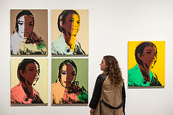 "© Licensed to London News Pictures. 10/03/2020. LONDON, UK. A staff member poses next to ""Ladies and Gentlemen (Alphanso Panell)"", 1975, (images of New York black and latino drag queens and trans women) by Andy Warhol. Preview of ""Andy Warhol"", a retrospective of over 100 works by one of the most recognisable artists of the late 20th century.  The exhibition runs 12 March to 6 September 2020 at Tate Modern.  Photo credit: Stephen Chung/LNP"