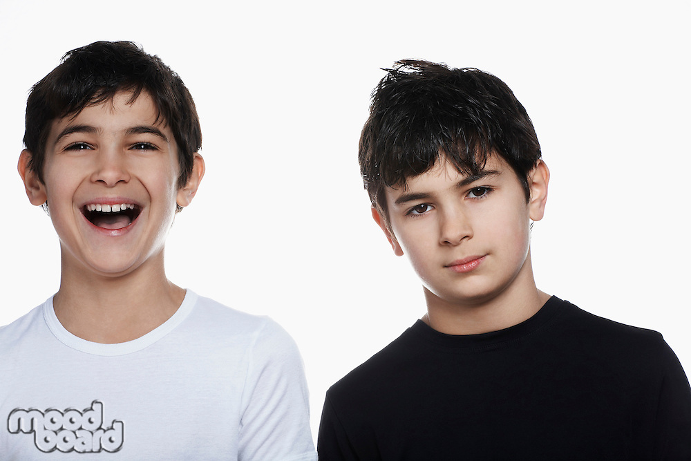 Studio portrait of twin boys (13-15) one laughing
