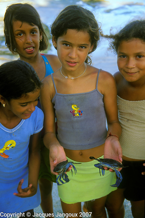 Girl of fishermen's village holding swimming crabs called siri in Brazil  at beach of fishing village in Alagoas State, Brazil.