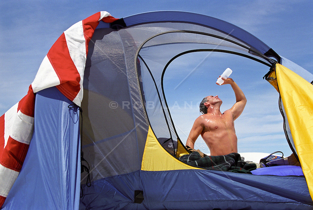 Shirtless man pouring water into his mouth beside his tent