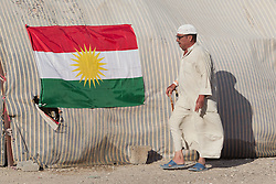 © Licensed to London News Pictures. 25/06/2014. Khanaqin, Iraq. An elderly Iraqi refugee walks past a Kurdish flag on the reception tent of a refugee camp on the outskirts of Bahari Taza village in Iraq. Located on the outskirts of Khanaqin, a town just 20 minutes from the front-line of the battle with ISIS insurgents, the Bahari Taza refugee camp, and its satellite camps, now house around 600 families from southern Iraq. Built by the local village leader to meet the influx of refugees from nearby Jalawla and Saidia, where intense fighting is still taking place. Turkman, Arab and Kurd, both Sunni and Shia, all live together in tents, barns and unfinished buildings waiting for the conflict to end. Photo credit: Matt Cetti-Roberts/LNP