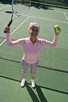 Senior woman on tennis court, portrait
