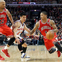 12 March 2012: Chicago Bulls point guard Derrick Rose (1) drives past New York Knicks point guard Jeremy Lin (17) on a screen set by Chicago Bulls forward Taj Gibson (22) during the first half of New York Knicks vs Chicago Bulls, at the United Center, Chicago, Illinois, USA.