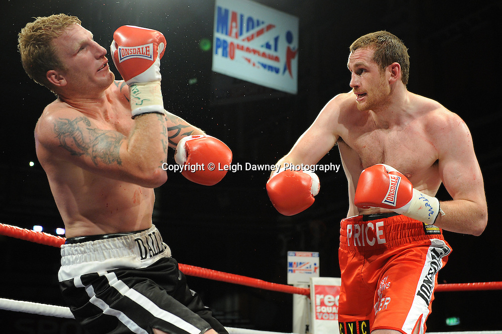 David Price (red shorts) delivers a heavy right hand knocking Tom Dallas to the canvas and claiming the British Heavyweight Title Eliminator contest at Olympia, Liverpool on the 11th June 2011. Frank Maloney Promotions.Photo credit: Leigh Dawney 2011