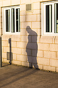 The shadow of a prisoner with his head down hits the wing wall between cell windows. HMP/YOI Portland, Dorset. A resettlement prison with a capacity for 530 prisoners.Portland, Dorset, United Kingdom.
