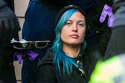 London, UK. 17 October, 2019. Metropolitan Police officers arrest campaigners against the arms trade from Extinction Rebellion Scotland who had glued or locked themselves onto the entrance to the headquarters of Leonardo UK in protest against the company profiting from 'guidance systems for missiles used in Yemen and Syria, as well as other media technology and telecommunications' and in solidarity with the Kurdish people following the Turkish invasion of Kurdish-held areas of north-east Syria.