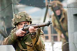 Renecator portraying a British Paratrooper from the 6th Airborne Division takes aim with his Lee Enfield rifle during a battle reenactment at Fort Paull Monday<br />