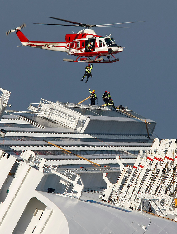 A rescue firefighter is winched up to a helicopter onto the cruise liner Costa Concordia off the west coast of Italy at Giglio island January 30, 2012. Search operations at the Costa Concordia resumed on Monday after being suspended for a day due to weather conditions and some movement of the capsized cruise ship...REUTERS/Darrin Zammit Lupi (ITALY)