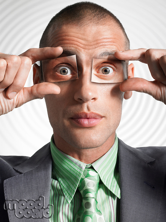 Businessman holding photos of eyes in front of his own eyes