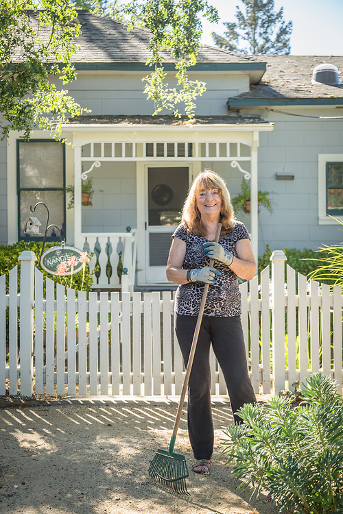 Nanci Smith sweeps up in front of her home in Calistoga