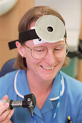 Portrait of staff nurse in aural care centre wearing head mirror and holding otoscope,