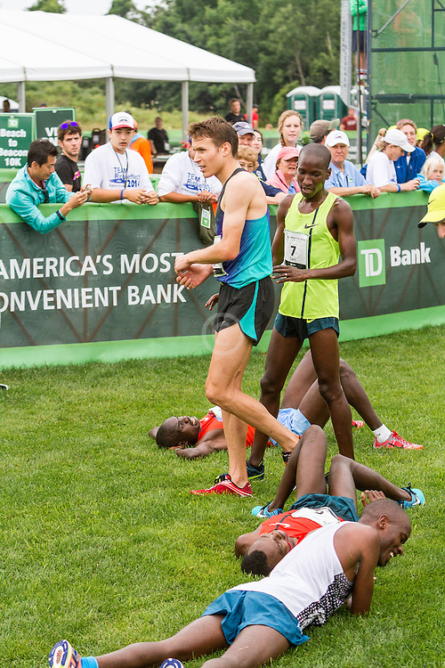 Ben True, Sam Chelanga, teammates, walk between other runner collapsed on grass afer finish
