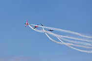 Canadian Forces Snowbirds performing a Lag Back Cross with smoke.  The Snowbirds are also known as the 431 Air Demonstration Squadron and fly the Canadair CT-114 Tutor jet. Photographed during the Canada 150 celebrations in White Rock, British Columbia, Canada.