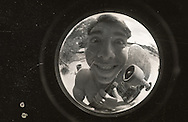 A skateboarder takes a break from a skateboarding session for a portrait as seen through a fisheye conversion lens.