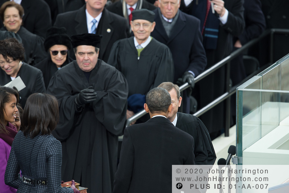 Chief Justice John Roberts congratulates President Obama after he is sworn in for a second term as Justice Antonin Scala makes an unusual face in the background during the 57th Presidential Inauguration of President Barack Obama at the U.S. Capitol Building in Washington, DC January 21, 2013.