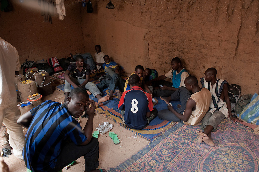 Young african migrants playing cards in their room in the ghetto