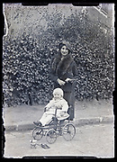 mother with happy smiling toddler in a stroller circa 1920s