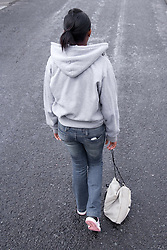Back view of young girl alone; dragging her bag along the street,