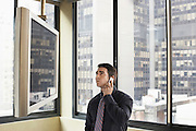 Businessman Using Cell Phone and Watching TV