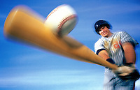 Male baseball player hitting ball with bat (blurred motion)