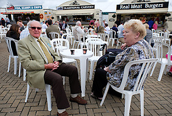 © Licensed to London News Pictures.14/07/15<br /> Harrogate, UK. <br /> <br /> A couple sit at one of the tables next to fast food stands on the opening day of the Great Yorkshire Show.  <br /> <br /> England's premier agricultural show opened it's gates today for the start of three days of showcasing the best in British farming and the countryside.<br /> <br /> The event, which attracts over 130,000 visitors each year displays the cream of the country's livestock and offers numerous displays and events giving the chance for visitors to see many different countryside activities.<br /> <br /> Photo credit : Ian Forsyth/LNP