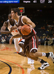 Brown forward Peter Sullivan (25) is guarded by Virginia guard/forward Mamadi Diane (24).  The Virginia Cavaliers defeated the Brown University Bears 74-50 in NCAA Basketball at the John Paul Jones Arena on the Grounds of the University of Virginia in Charlottesville, VA on January 6, 2009.