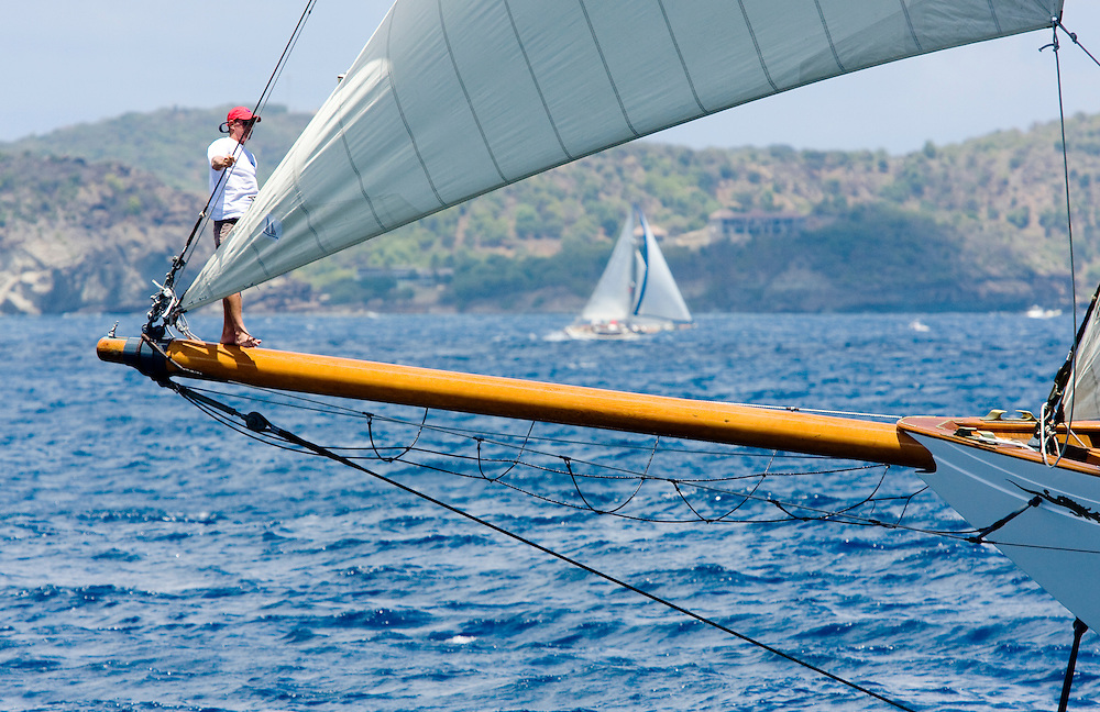 An unidentified crew member keeps watch from the bowsprit of the schooner yacht whose name is SY Altair during the 2008 Antigua Classic Yacht Regatta . This race is one of the worlds most prestigious traditional yacht races. It takes place annually off the costa of Antigua in the British West Indies.