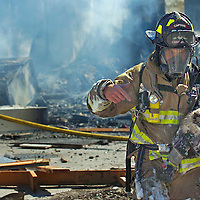 Livingston Fire Captain Chris Burha carries Mitzi, a house cat, away from a structure fire in Livingston, Mont. Burha found the cat underneath a bed after much of the house had already burned. Firefighters from Park and Gallatin Counties responded to the fire after a Natural Gas explosion ignited two houses and a garage.