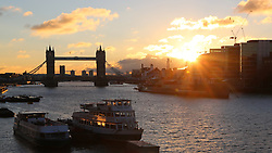 © Licensed to London News Pictures. 11/01/2014. A bright sun eventually appeared in the Upper Pool of the Thames after sunrise. After a wet and cloudy start to the day, London saw bright sunshine and blue skies. Credit : Rob Powell/LNP