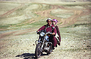 photos from travels in Mongolia - couple with goat on motorcycle, winding jeep track roads behind<br /> <br /> <br /> Photo must be credited to &quot;Jacques-Jean Tiziou / www.jjtiziou.net&quot; adjacent to the image. Online credits should link to www.jjtiziou.net. Photo may only be used as permitted by the photographer.