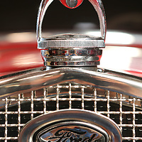 The radiator cap and grill of a 1931 Ford Model A street rod that has a 320 cubic inch engine, automatic transmission, foose wheels, fully chromed and powdercoated undercarriage.