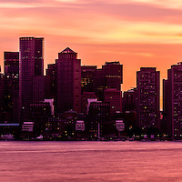 Boston panoramic skyline sunset photo. The sky is a beautiful shade of purple and orange as the sun sets over Boston Harbor. Panoramic photo ratio is 1:3.