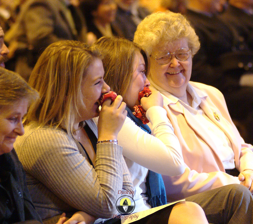 "BATH, Maine -- 12/16/ 06 -- Faye Hart, of Bath, shares a happy memory of her husband, Jack with her granddaughters during the funeral.  John C. ""Jack"" Hart Jr. was a  Bath City Councilor and Fireman. Photo by Roger S. Duncan ."