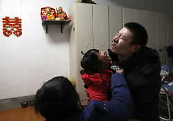 epa05751041 (20/22) Chinese migrant worker Wang Pengfei (C) shares an intimate moment with his son Ruiqi (R) and daughter Yaqin (L) in their home in Heze City, Shandong Province, China, 22 January 2017. Wang is the migrant worker and is working in the capital city as a delivery man. He will travel to visit his family in the Shandong Province for the annual Chinese Lunar New Year or Spring Festival. This is the only time he gets to see his family each year. Wang will join millions of fellow Chinese travelers making their way back home as they pack trains, planes and buses, in what is the largest human migration in the world. The journey, known as 'Chunyun' - the annual spring migration, will involve a total of 2,98 billion trips, starting from 13 January and continuing until 21 February 2017.  EPA/HOW HWEE YOUNG PLEASE REFER TO THE ADVISORY NOTICE (epa05751021) FOR FULL PACKAGE TEXT