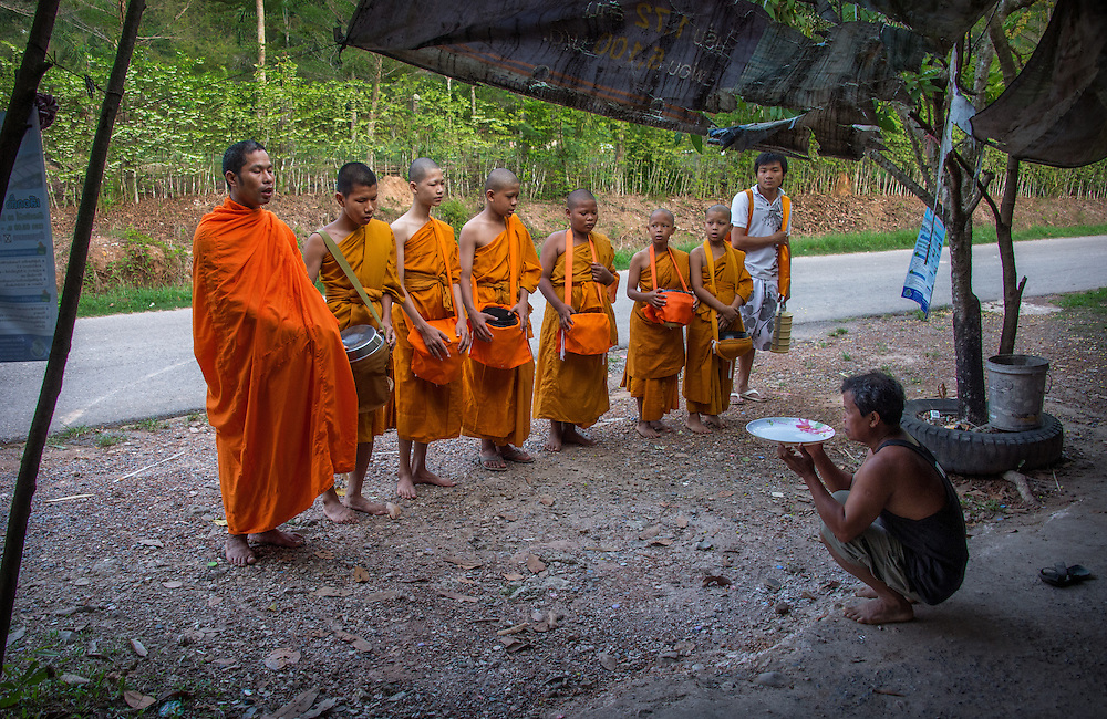 Young novice monks walk for alms in rural Nakhon Nayok, Thailand.