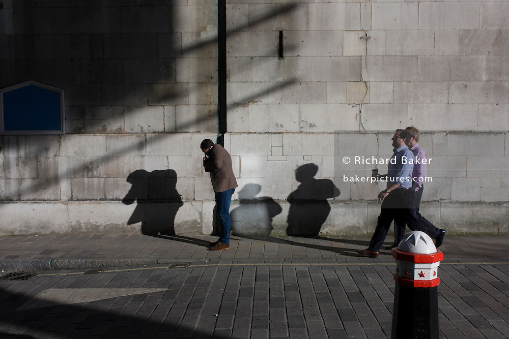 City of London bollard and businessmens' shadows on church wall.